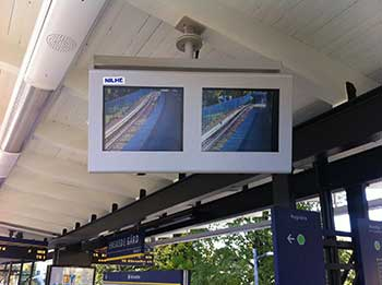 Custom built dual, side-by-side monitor enclosure on a train platform